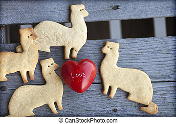 Love Background with sugar cookies shaped as ferrets on a wooden table background with little red heart, Valentines day background