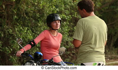 girl in helmet sits on scooter and listen to instructor -...
