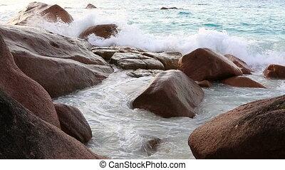 Waves breaking on granite boulders in beach of Anse Lazio...
