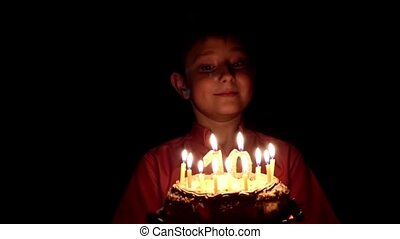 The birthday boy blows out the candles on cake slow motion, black background