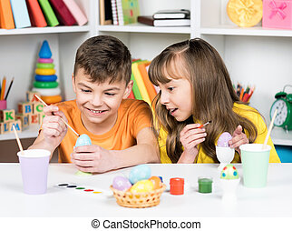 Easter holiday - cute children coloring eggs for easter at...