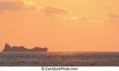 ship on horizon of sea at sunset