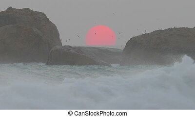 red sun is setting in the sea between the rocks - big red...
