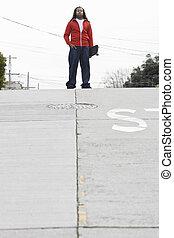 Teen Boy Standing with Skateboard