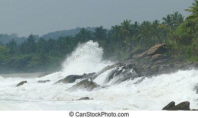 ocean waves breaking on rocks of tropical coast - Large...