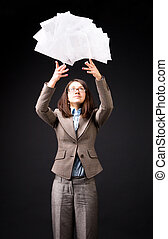 Young businesswoman throwing up heap of papers On dark...