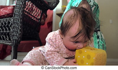 Baby Eating Play Cube - A confused baby is trying to eat a...