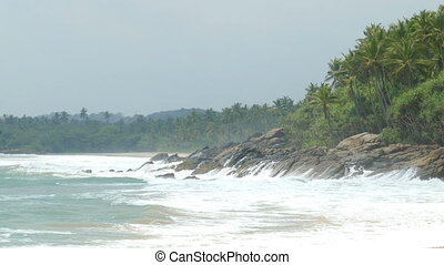 ocean waves breaking on rocks of tropical coast - Large...