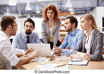 Business meeting - Group of business partners listening to...