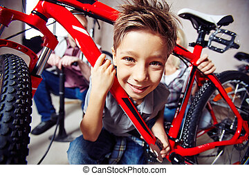 Cute boy with wrench looking at camera