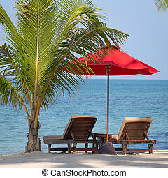 Two beach chairs, red umbrella and palm tree on the beach in...