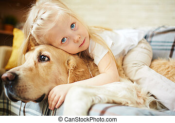 Cuddling dog - Cute child lying on fluffy pet