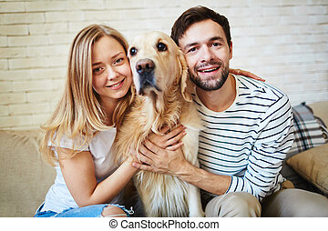 Couple with dog - Happy young couple and their pet spending...