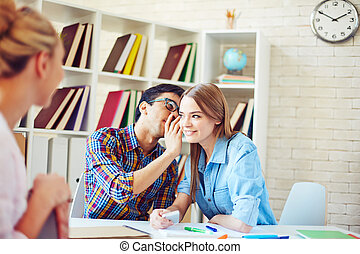 Telling secret - Handsome guy whispering secret to cute girl