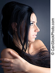 Young brunette woman profile portrait On dark background