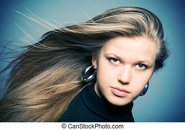 Woman with fluttering hair. On blue background.