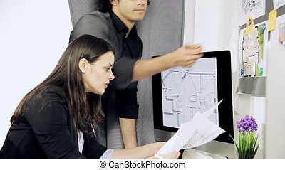 Two architects at work in office on house project
