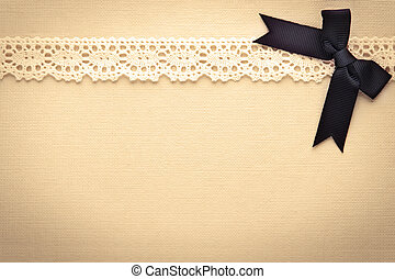 Retro lace and bow over real hand made paper background.