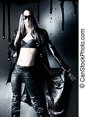 Goth woman with black raincoat. On wall background.