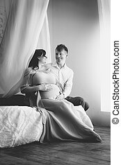 Black and white shot of elegant pregnant couple relaxing on...