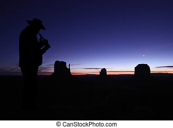 Man Playing Flute in Desert at Dusk - Mid adult male wearing...