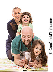 Happy family piled on top of little girl home having fun...
