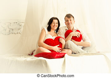 Toned photo of pregnant couple posing on big bed with...