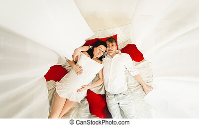 happy husband hugging pregnant wife on big bed with...