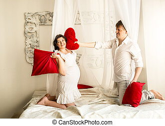 pregnant woman having pillow fight with husband on bed with...
