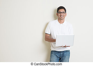 Indian man using computer - Portrait of handsome Indian guy...
