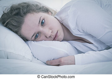Sad tired woman - Close-up of young sad tired woman lying in...