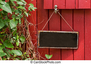 Empty metal sign in front of a red wooden wall