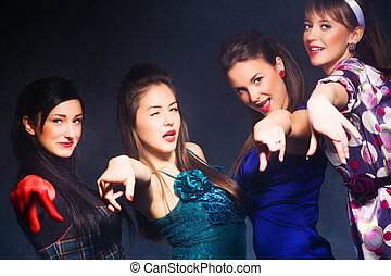 Cheerful party. Four women pointing to the camera.