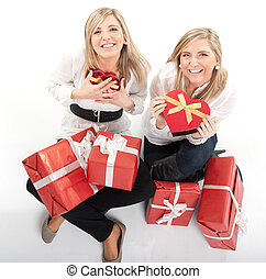 Special occasion - Two young sisters surrounded by gift...