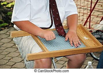 boy playing the washboard - Young boy playing an...