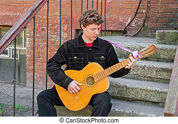 Guitarist from slums - Guitarist playing his guitar of...