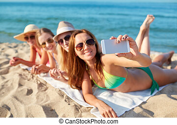 close up of smiling women with smartphone on beach - summer...