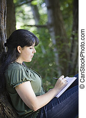 Young Woman Writing in Journal - Young Woman Sitting in...