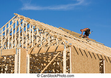 Carpenter Building Roof - Carpenter uses a pneumatic nail...