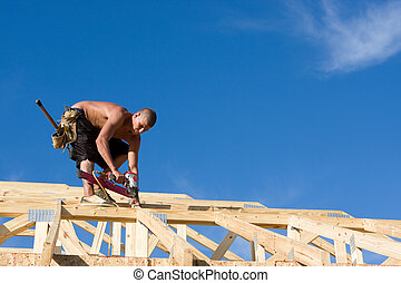 Carpenter Using Nail Gun - Carpenter uses a pneumatic nail...