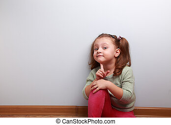 Fun smiling sitting kid girl thinking with finger near face...