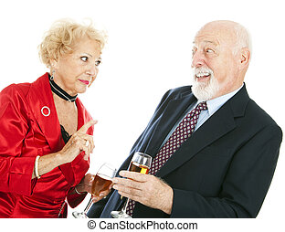 Now You Behave - Senior couple at a party. The husband is...