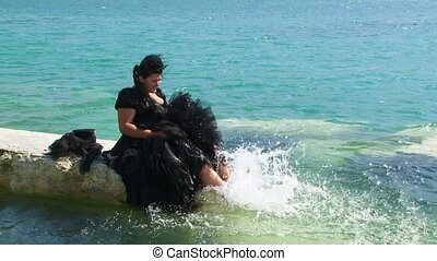 Black Haired Woman In  Full Dress Splashing Water  on the  Lake With Legs