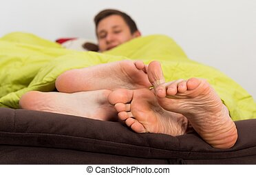 Pleasure in Bed - Young man showing toes up for excellent...