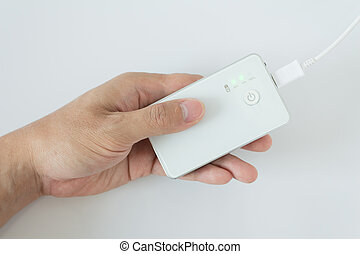 male hand plugging in the plug of his power bank in a socket