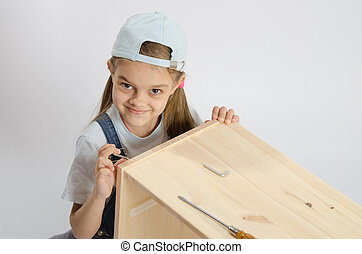 Little girl in image collector of furniture turn screw -...