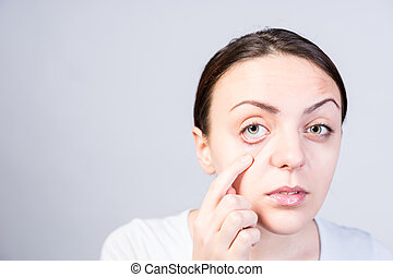 Young Woman Pulling Down her Lower Eyelid - Close up Pretty...
