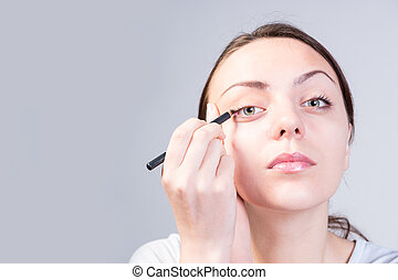 Serious Young Woman Applying Eyeliner on Right Eye - Close...