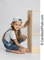 Little girl in overalls collector of furniture turn screw on...