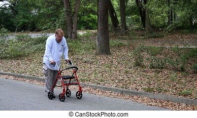 Disabled Man Using Walker - Disabled man walks at the side...